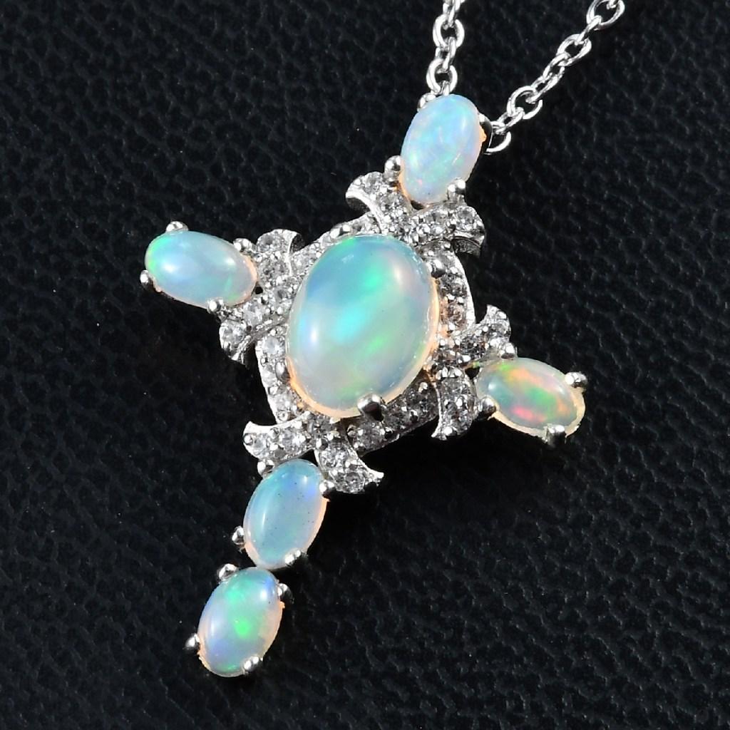 Welo Opal cross pendant on black surface.