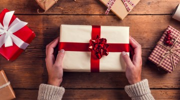 Man holding onto wrapped Christmas gift