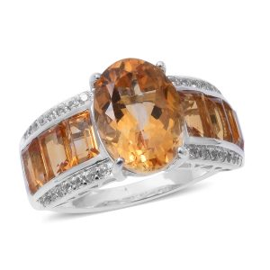 Orange citrine ring against white background.