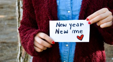 """Woman holding a """"new year, new me"""" sign"""