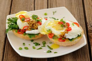 English muffin topped with runny eggs and seasonings.