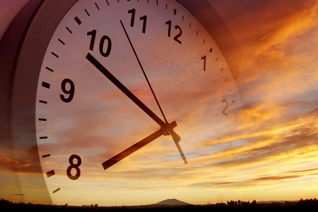 Clock face against dawn or dusk sky.