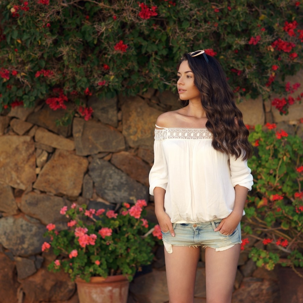 Woman in white top and denim shorts against roses.