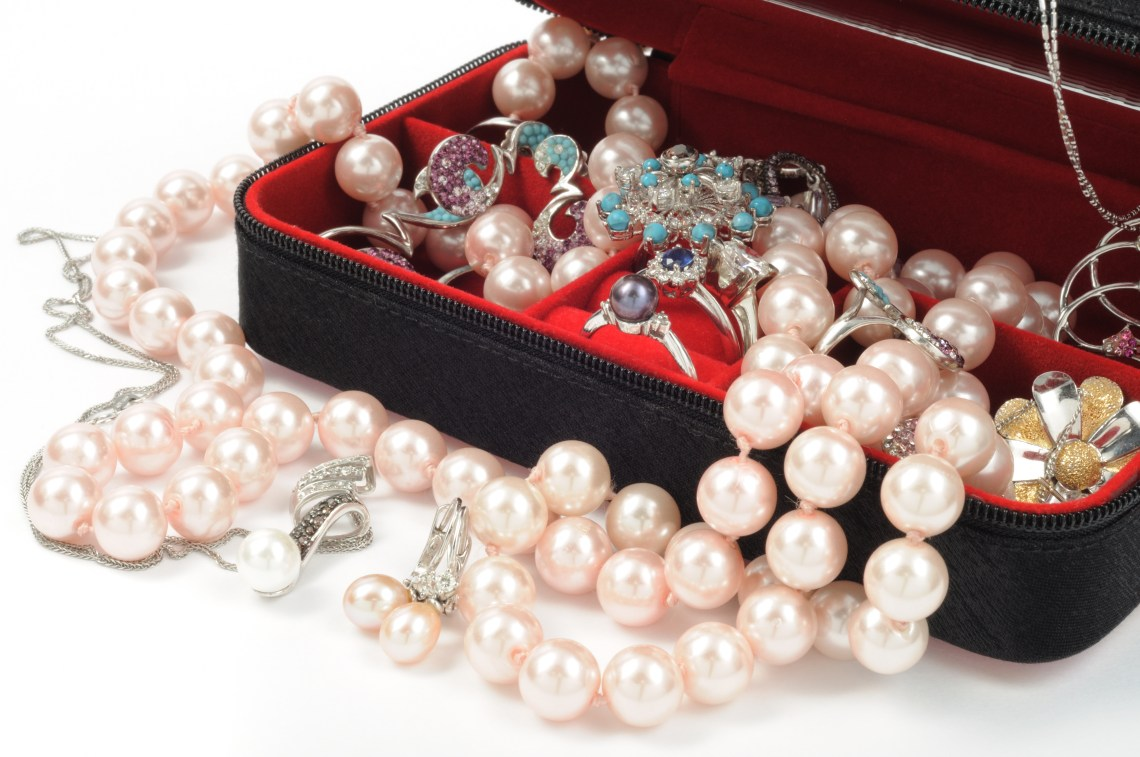 Assortment of pearl jewelry overflowing from jewelry box.