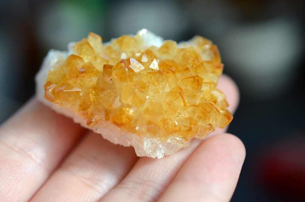 Small citrine geode resting on fingers.