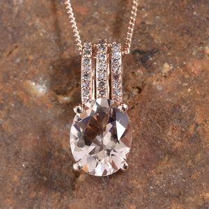 Morganite and pink diamond pendant resting on stone.