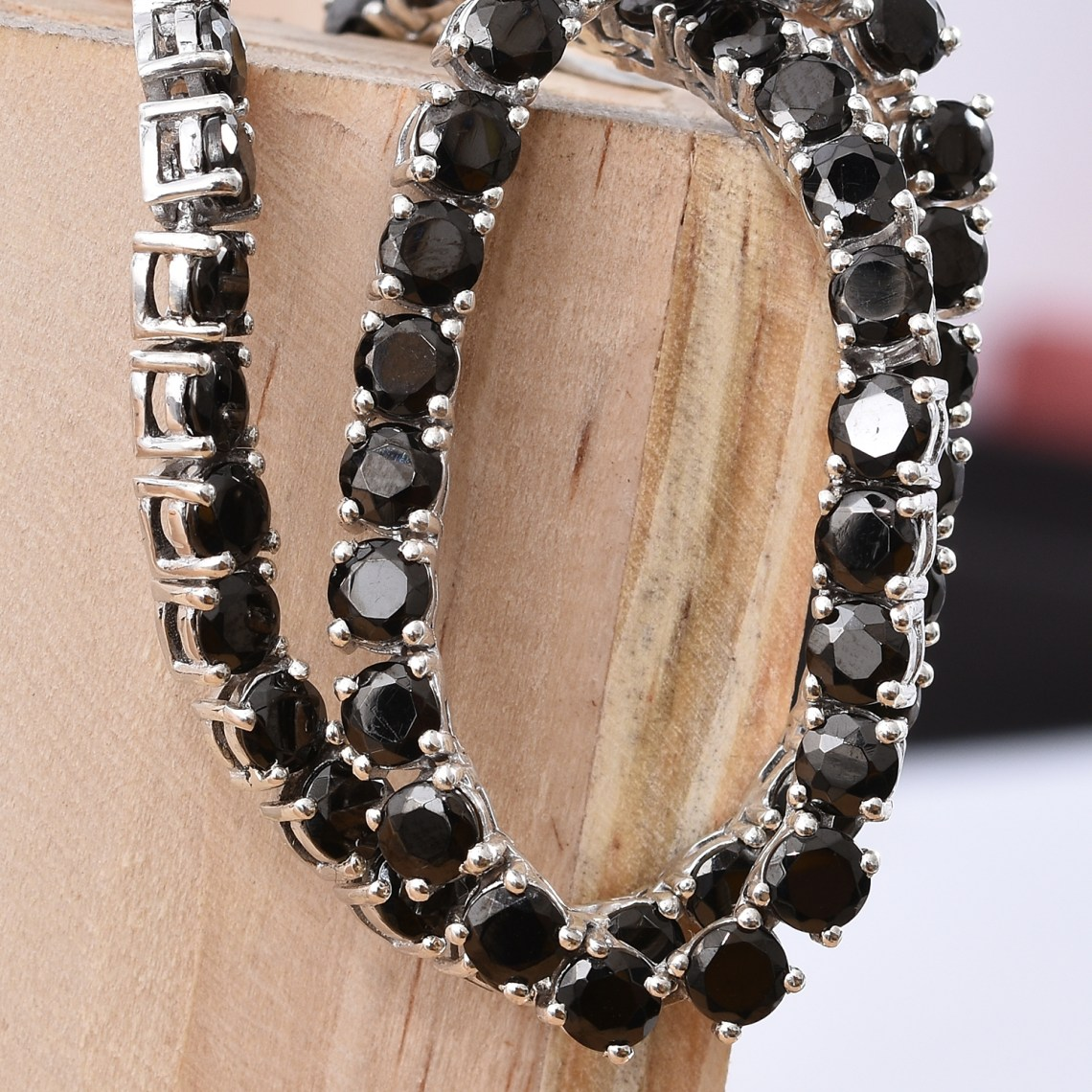 Shungite necklace draped over light colored wood.
