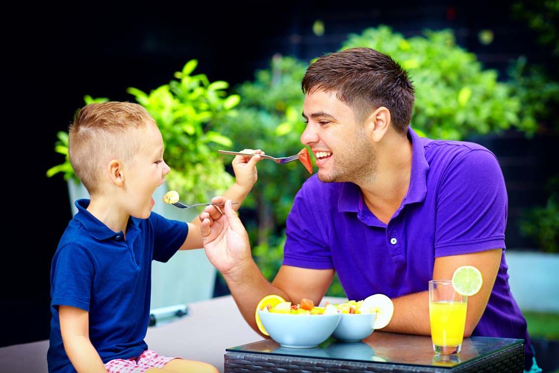 Father and son feeding each other a home cooked meal.