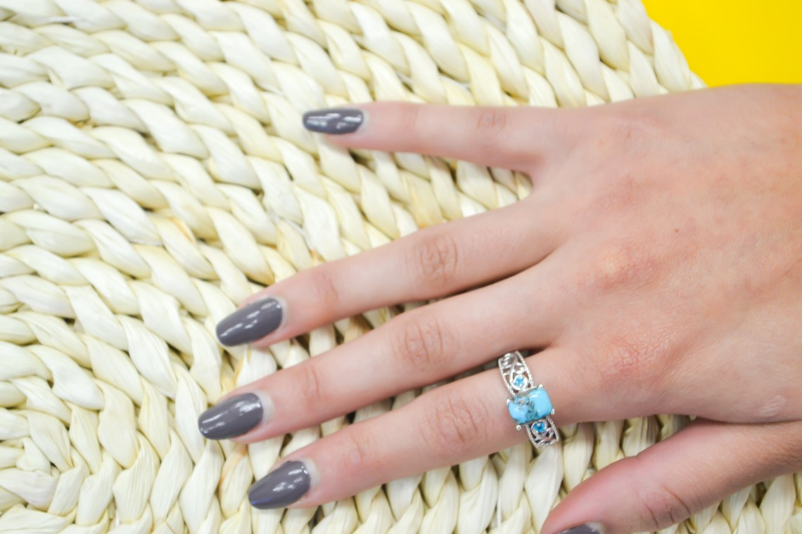 Woman's hand on woven mat, wearing turquoise ring.