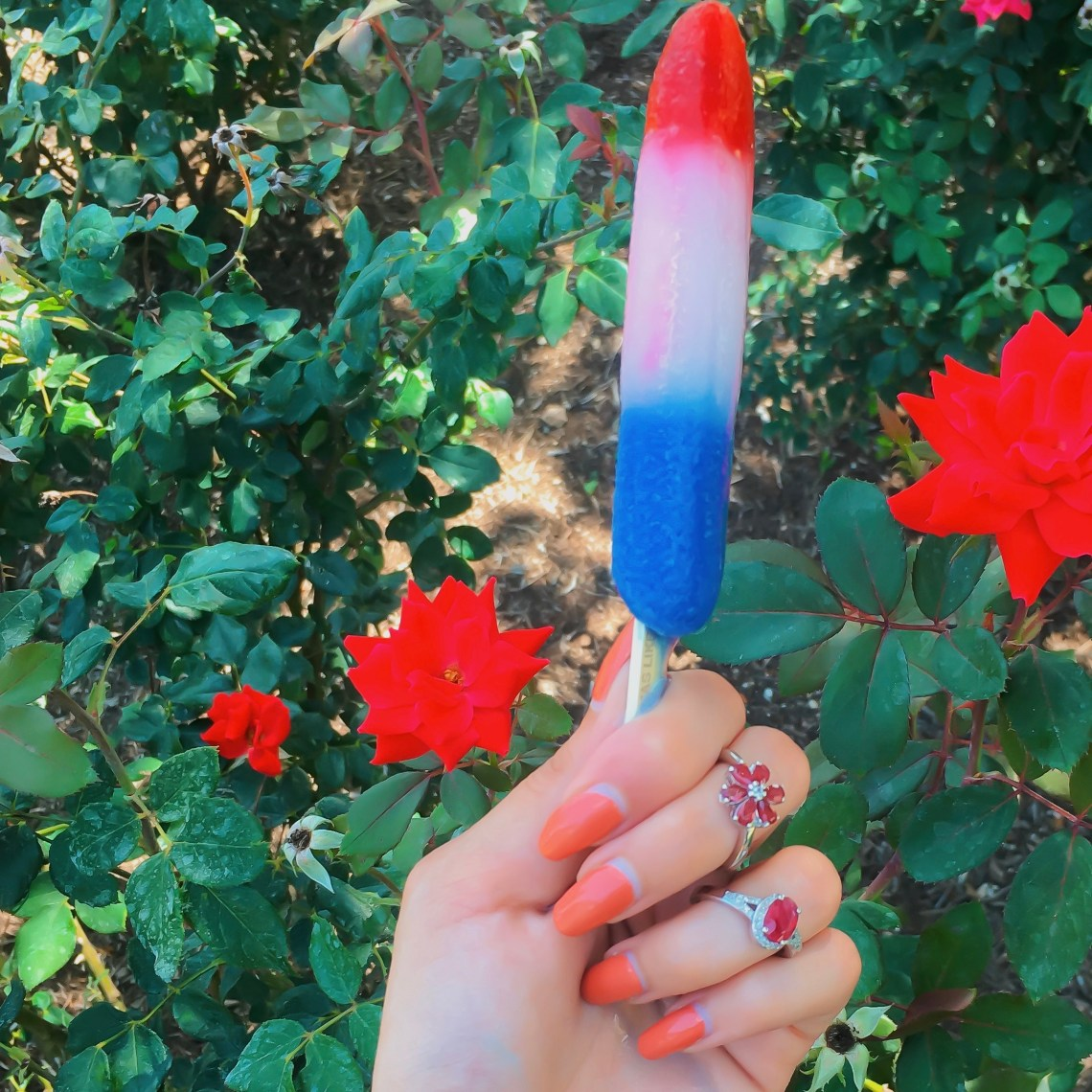Woman's hand holding popsicle and wearing ruby rings.