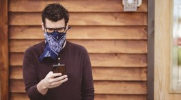 A male wearing glasses and a scarf as a face mask using his phone in front of a wooden wall.