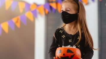 Girl wearing mask that matches with her costume.