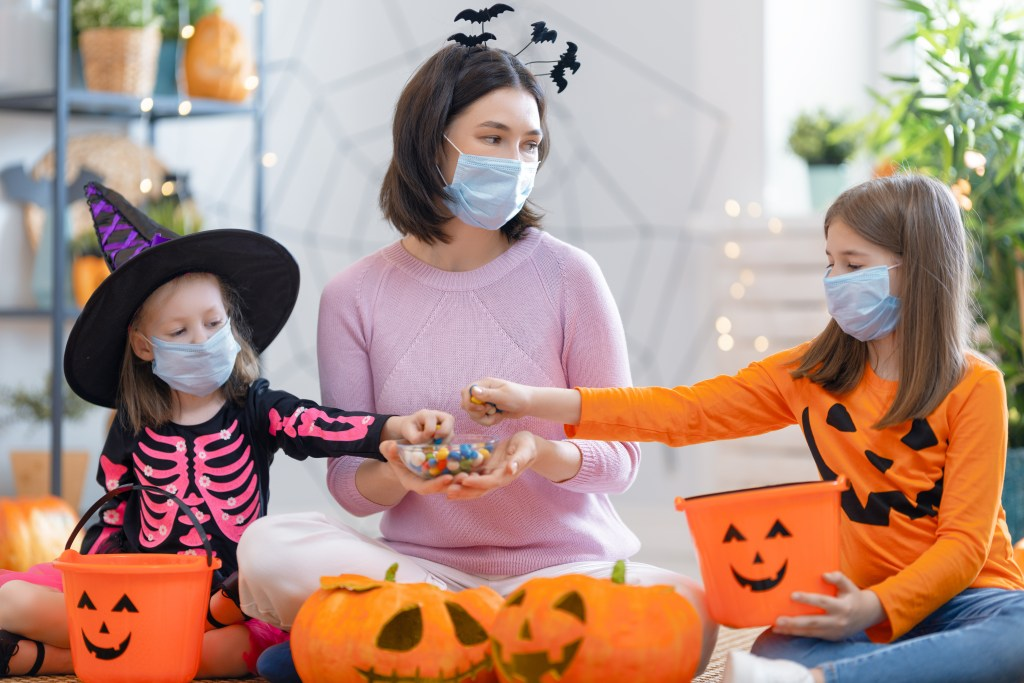 Family wearing masks while sorting candy.