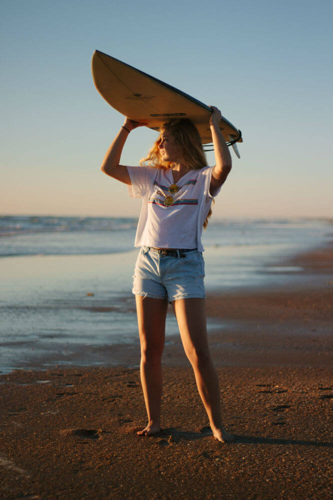 Chica en la playa con tabla de surf y shorts denim
