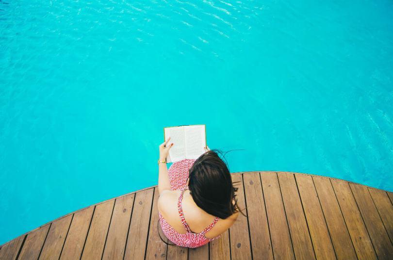 mujer leyendo libro en una piscina