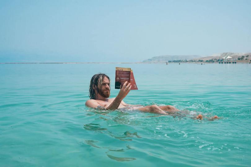 hombre leyendo libro en el mar
