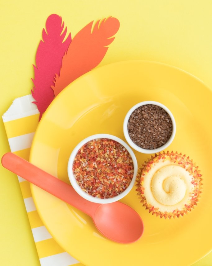 Fall Cupcakes With Fall Sprinkles on yellow dish and paper feathers