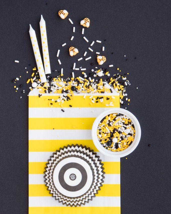 Bumble bee party supplies and bee party sprinkles on black background