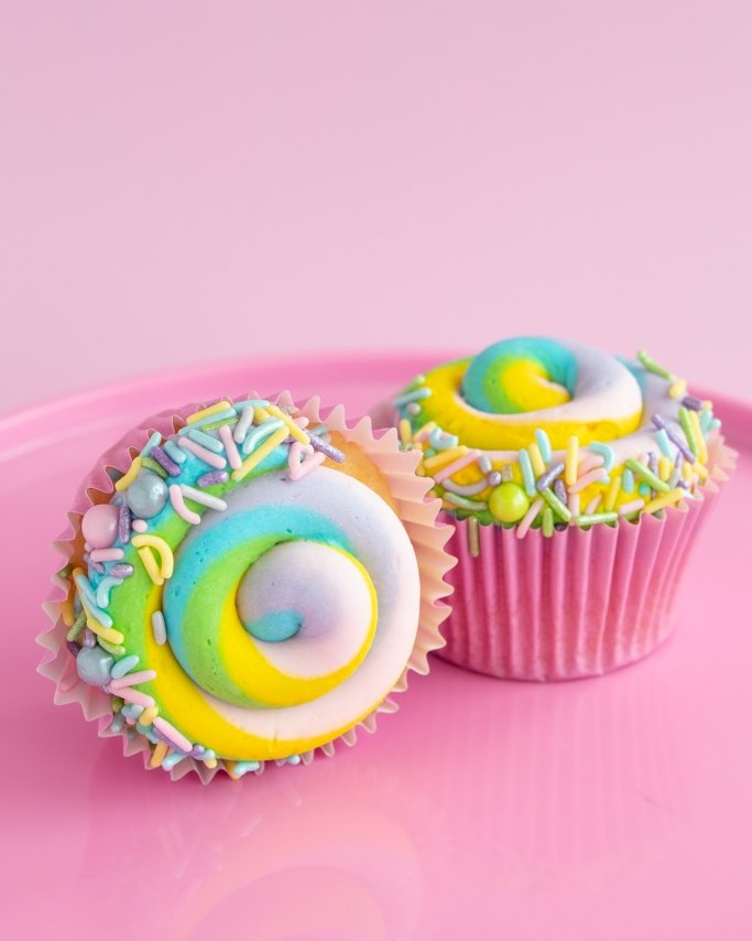 Pastel Easter Cupcakes with pastel sprinkle mix trim on pink plate and light pink pastel background