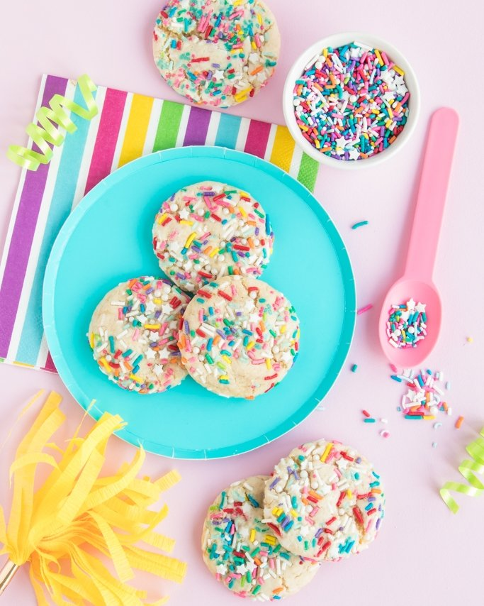 Funfetti Cake Mix Cookies Recipe - Rainbow sprinkles on top of white cake mix cookies on blue plate and rainbow party supplies around