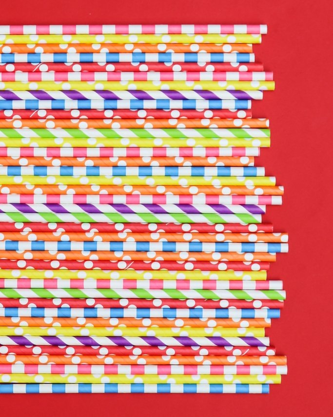 bubble gum party ideas - rainbow paper straws assortment on red background