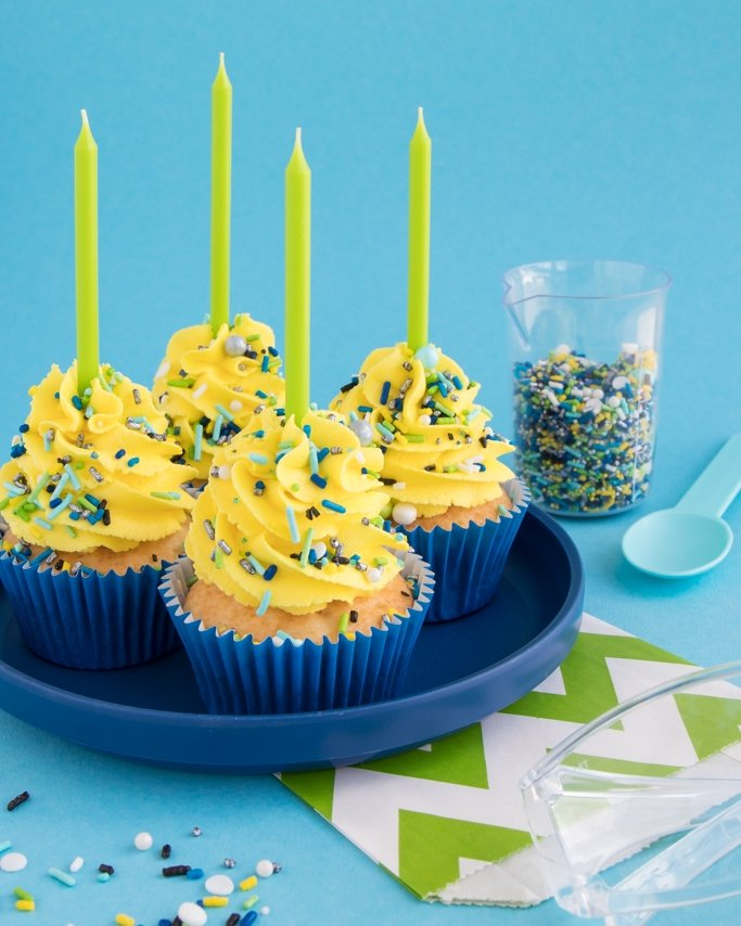 Mad Science Party Cupcakes topped with sprinkles and lime green candles on navy plate