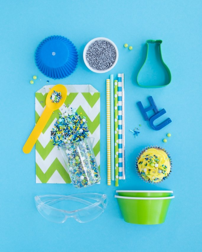 Mad Science Birthday Party Supplies with beaker, flask, and safety glasses on blue background