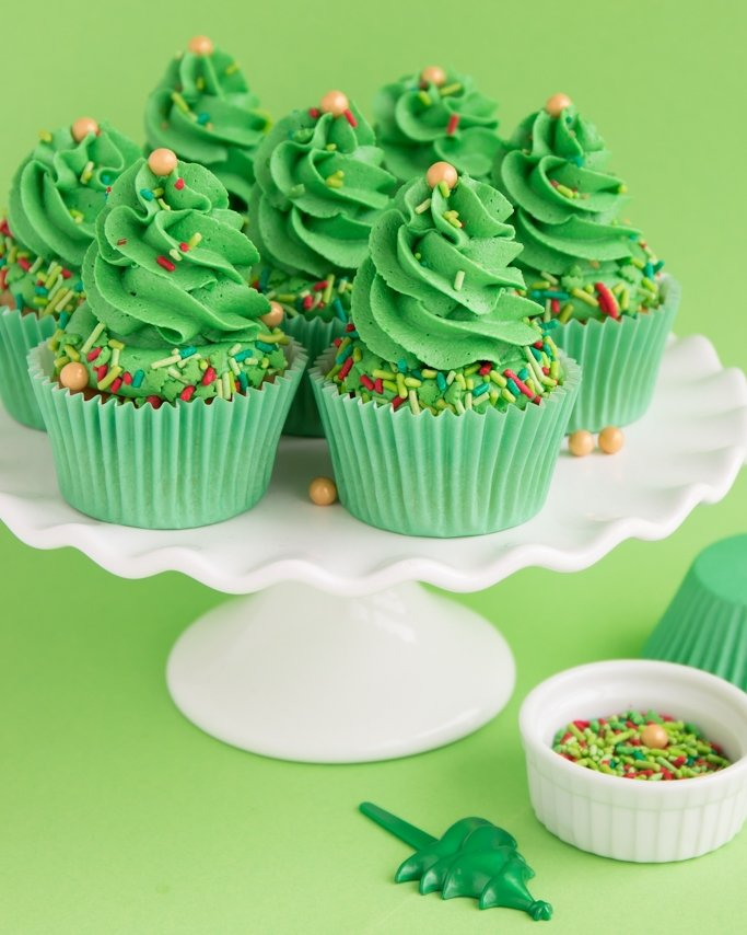 Christmas Tree Cupcakes on white cake plate and green background with Christmas sprinkle mix