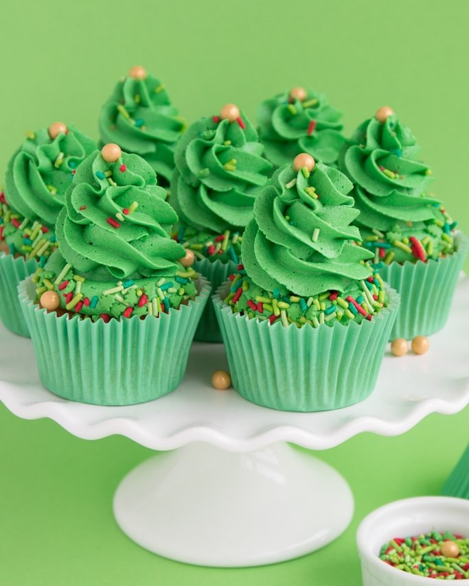 Christmas Tree Cupcakes on white cake plate and green background with Christmas sprinkles