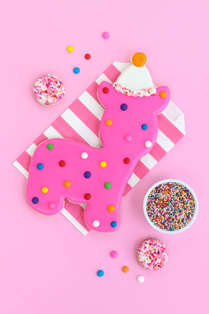 Huge dot circus animal cookie on pink striped paper favor bag with sprinkle cookies around
