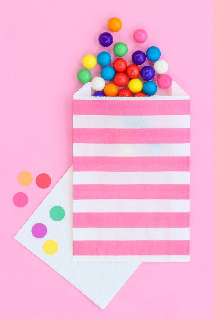 Pink stripe paper favor bags with gumballs pouring out