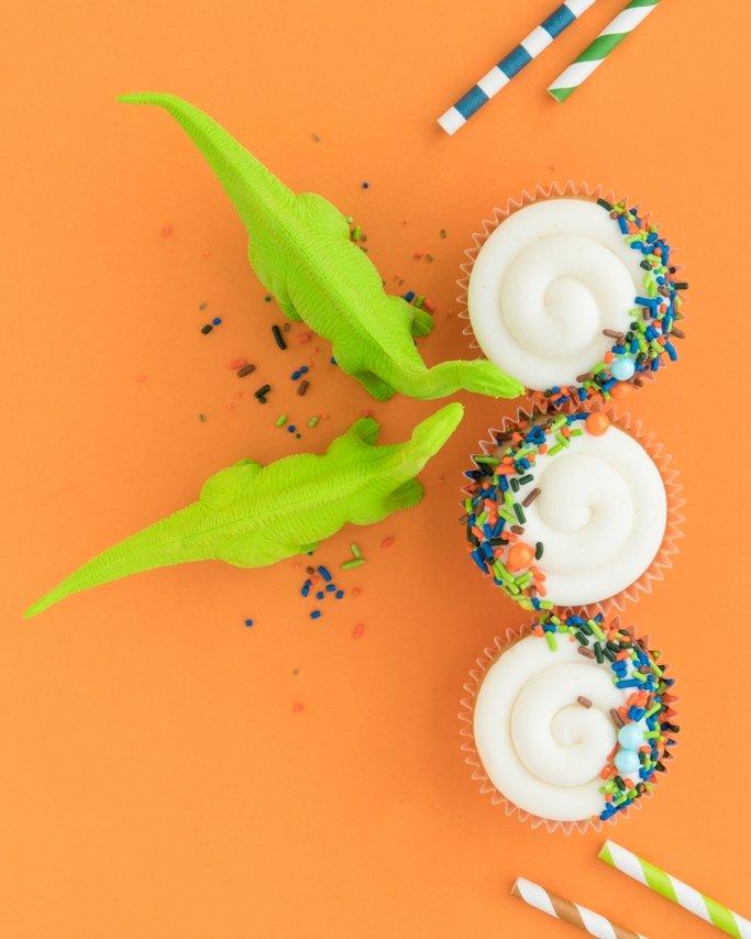 Dinosaur Birthday Party Cupcakes with toy dinosaurs on orange backaground