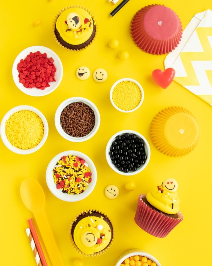 Emoji Party Ideas - Emoji Party Supplies laid out with Emoji sprinkles on yellow background