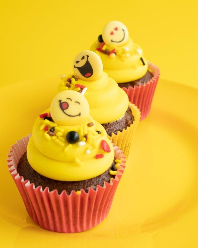 Emoji Cupcakes with Emoji sprinkles in red greaseproof cupcake liners on yellow background