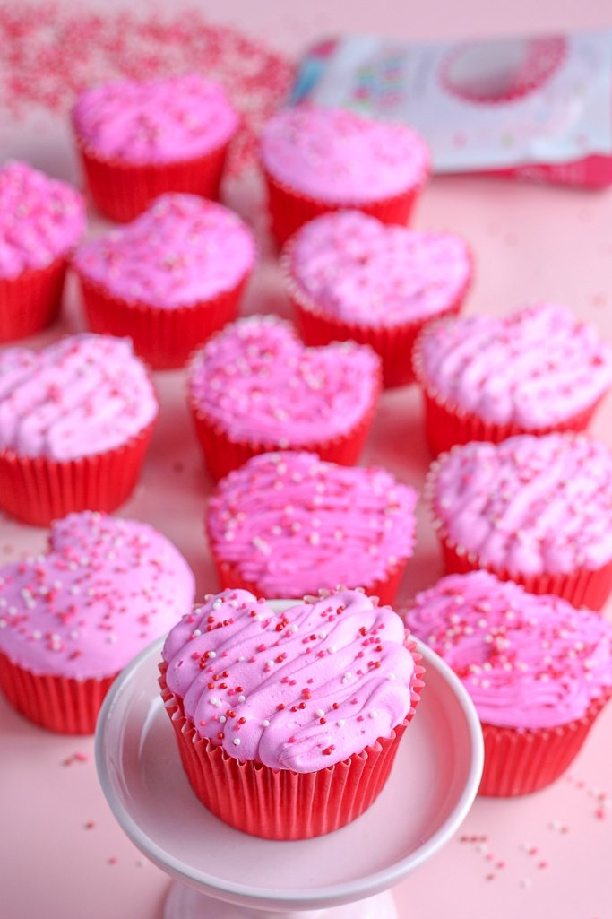 a heart cupcake on a stand with the others in the background