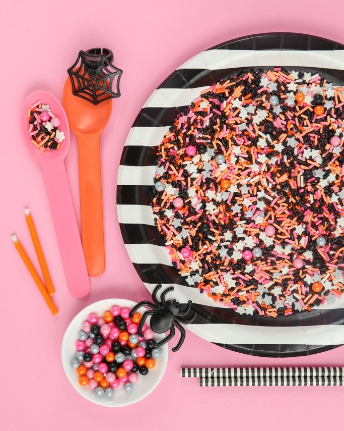 Hocus Pocus Halloween Sprinkle Mix on black striped plate on pink background