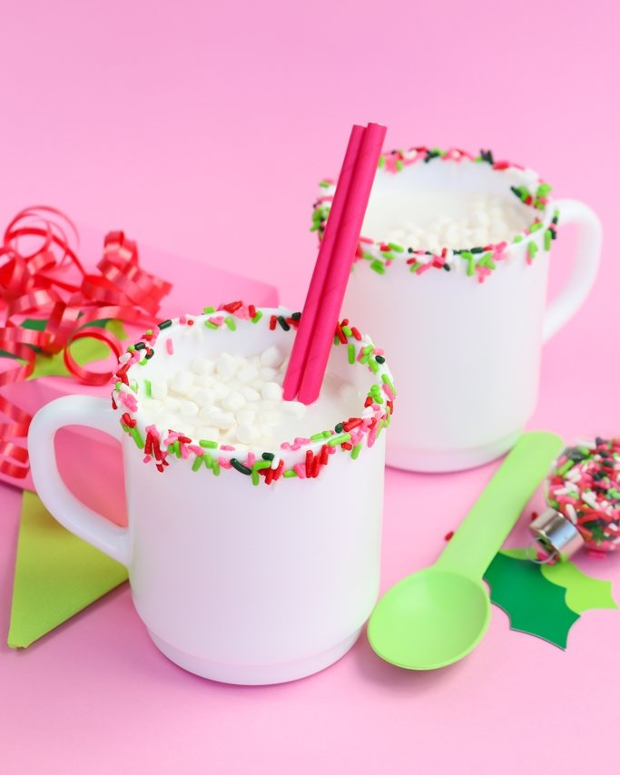 Girly christmas party ideas - hot cocoa in sprinkle rim mugs on pink background