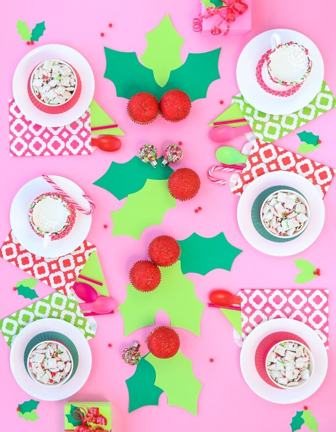 Girly modern Christmas party table with 6 place settings and holly cupcakes, christmas puppy chow and more on pink background.