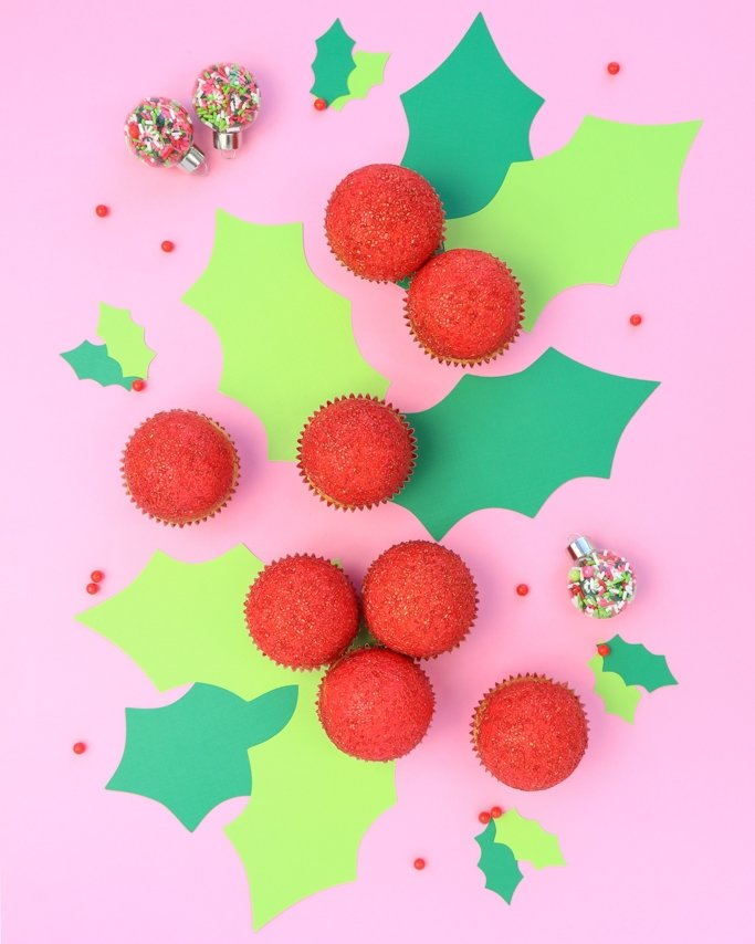Holly Christmas Cupcakes - topped with red sugar crystals with holly cutout leaves on pink background.