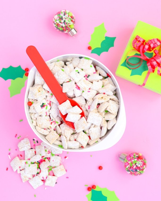 White Chocolate Christmas Puppy Chow - Christmas Muddy Buddies on pink background with wrapped presents around