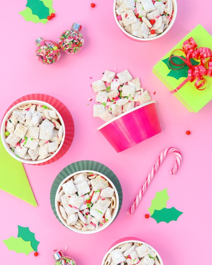 white chocolate christmas puppy chow christmas muddy buddies in treat cups on pink background and - Christmas Puppy Chow