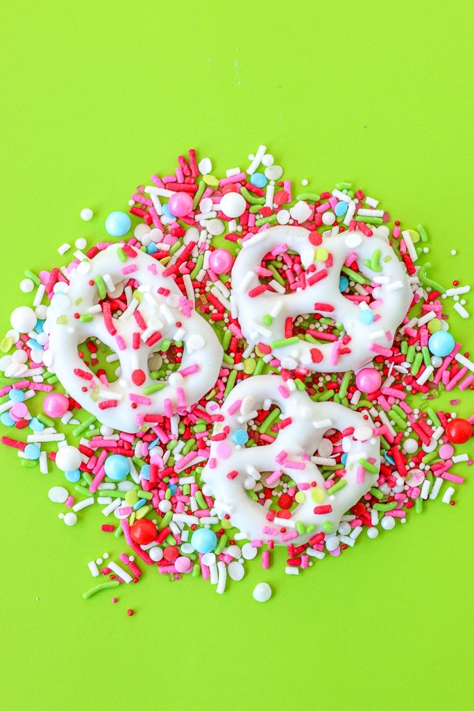 A few of the finished chocolate covered pretzels on a pile of sprinkles ready to be enjoyed.