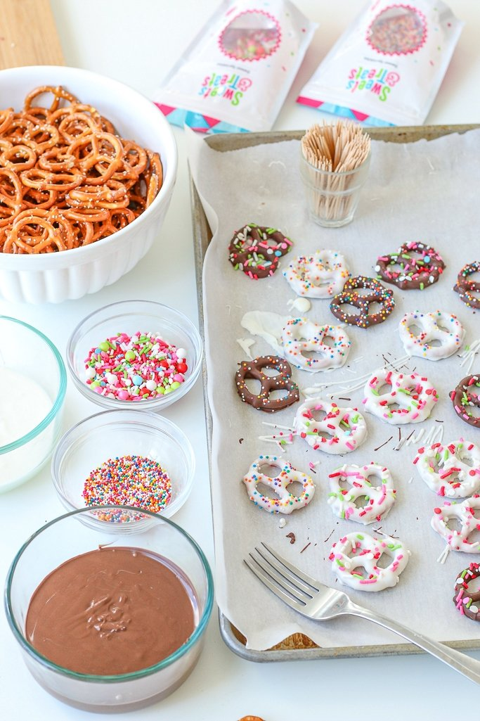 Image shows the chocolate covered pretzels on a tray, decorated and ready to enjoy along with the supplies to make them.