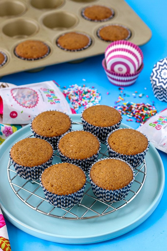 A final image showing the finished cupcakes on a cooling rack. Filling cupcake liners was easy and fun!