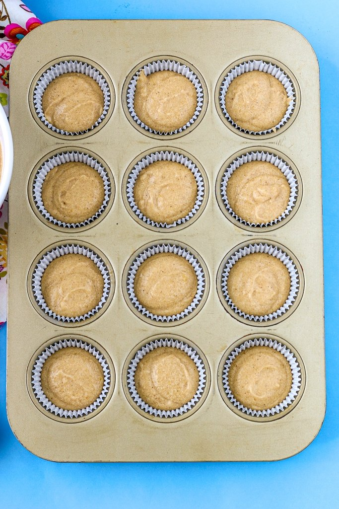 Image of the answer to how much do you fill cupcake liners! A full pan of full cupcake liners ready for the oven with the same amount of batter.