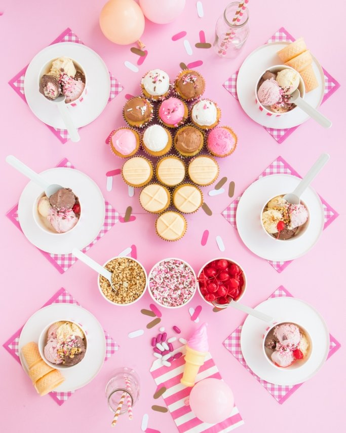 Ice Cream Party Ideas - 6 place tablescape with ice cream cone cupcake cake and Neapolitan sprinkles on light pink background