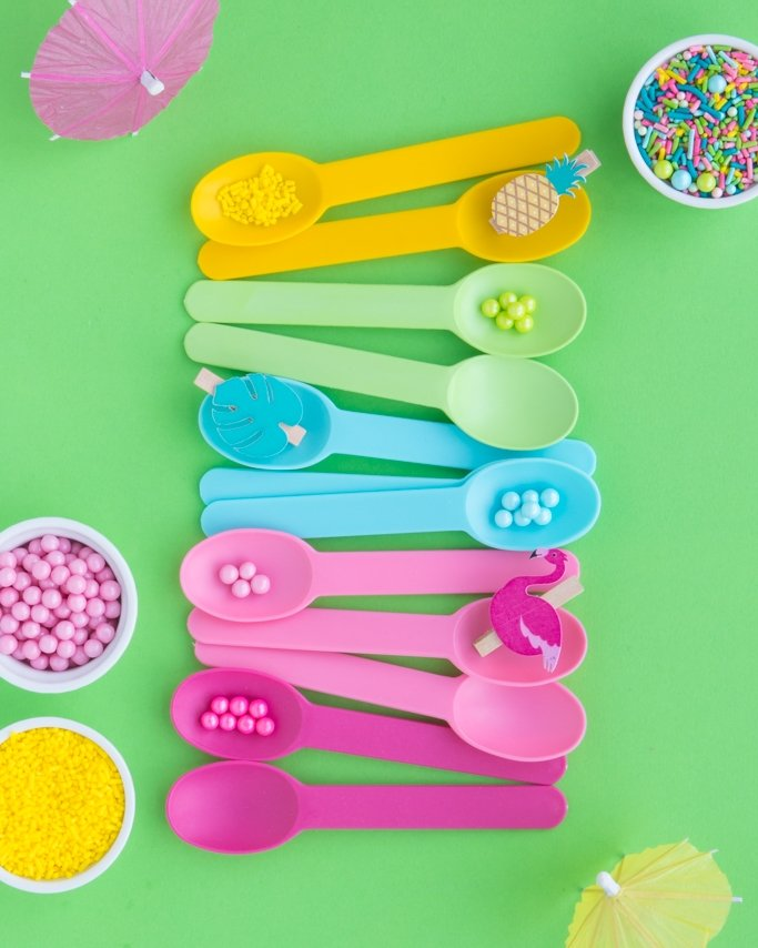 Luau Party Supplies and Ice Cream Spoon on green tropical background
