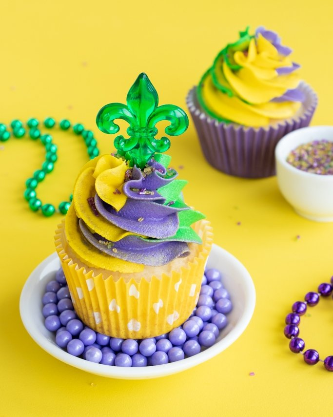 Mardi Gras Cupcakes on bed of purple sugar pearls on yellow background