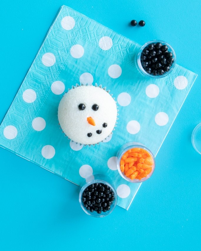 adding sugar pearls for the snowman mouth on the cupcakes