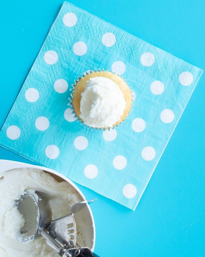 vanilla buttercream on baked cupcake for snowman cupcakes